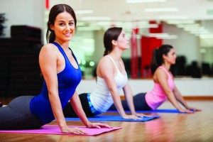 3-women-doing-exercise-in-the-yoga-class-on-yoga-mats-inside-gym